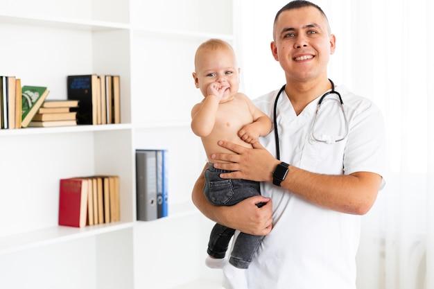 Medico sorridente che tiene piccolo bambino adorabile