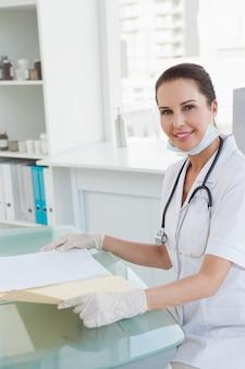 Medico sorridente che tiene un archivio medico