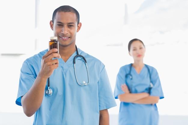 Medico sorridente che tiene una bottiglia di pillole con il collega