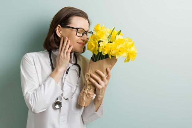 Medico sorridente della donna con il mazzo dei fiori