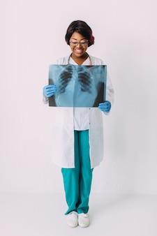 Medico sorridente della donna dell'afroamericano dei giovani in vestiti medici che tengono i raggi x del paziente