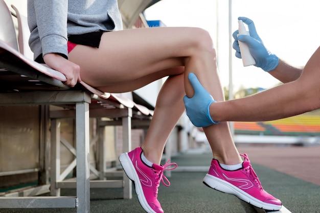 Medico sportivo che cura il ginocchio dello sportivo ferito.