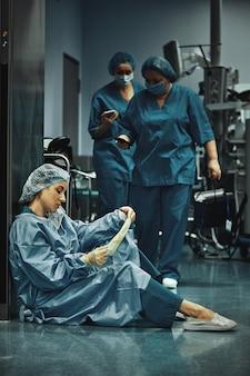 Medico stanco che si siede dopo l'intervento chirurgico nel corridoio dell'ospedale