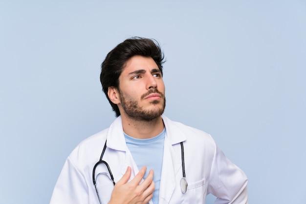 Medico uomo in piedi e pensando un'idea