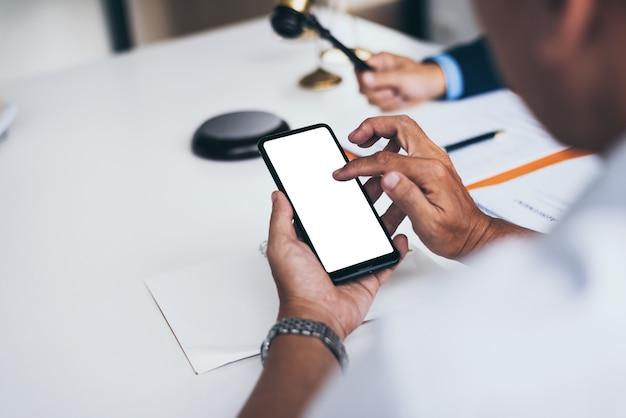 Medioevo due avvocati di sesso maschile che lavorano con smart phone in ufficio con il martelletto.
