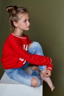 Meditabonda bella ragazza seduta su un cubo bianco e in posa, modelli di scuola. primo piano serio del ritratto della ragazza su colorato. ,