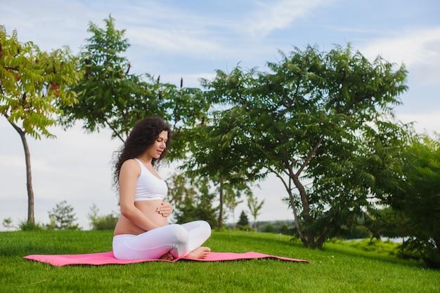 Meditando donna incinta nel parco.