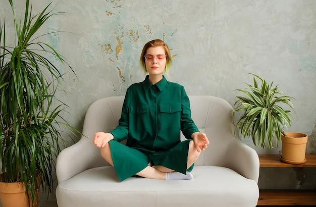 Meditazione con un telefono in mano, respirazione profonda. applicazione di meditazione mobile. la giovane donna di concetto sitizen si rilassa e medita in un interno moderno. del millennio.