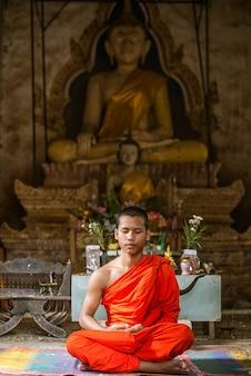 Meditazione del monaco dei novizi davanti alla statua di buddha.