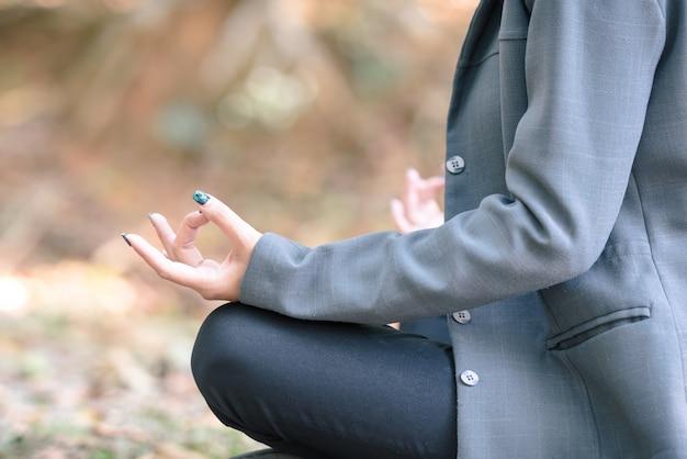 Meditazione yoga della donna d'affari nel parco naturale.