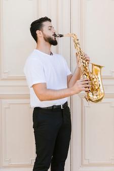 Medium shot lateralmente musicista che suona il sax