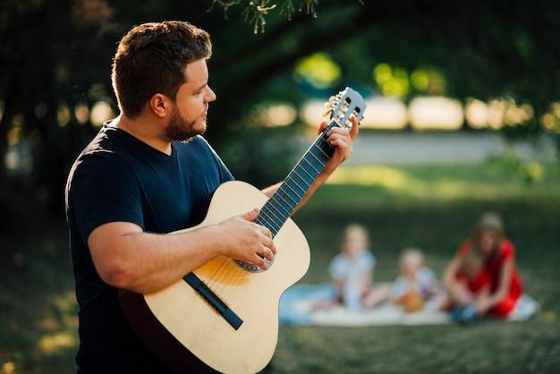 Medium shot lateralmente padre a suonare la chitarra