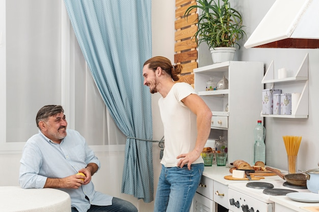 Medium shot padre e figlio, parlando in cucina