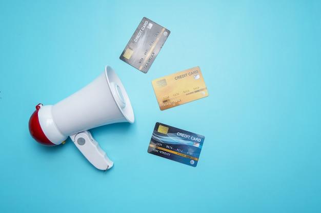 Megafono con la carta di credito sulla parete blu, concetto di relazioni pubbliche di interesse economico