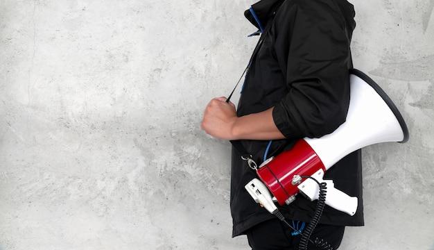 Megafono della holding del giovane sulla priorità bassa del muro di mattoni