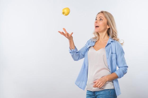 Mela di lancio della giovane donna bionda emozionante nell'aria contro il contesto bianco