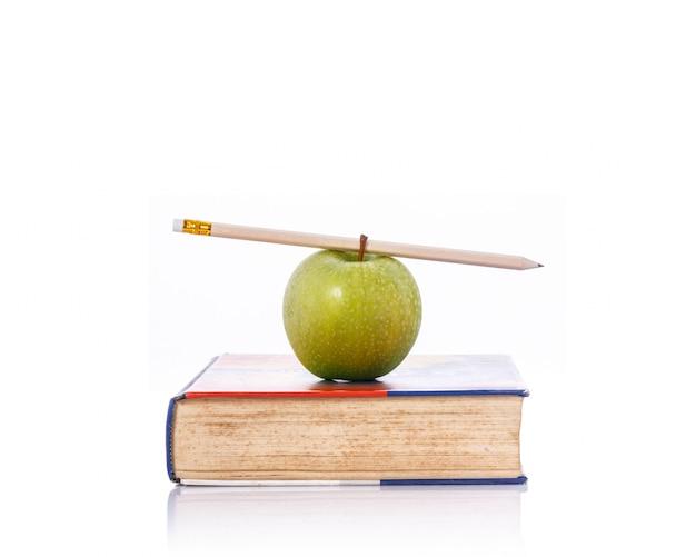 Mela e matita verdi sul libro.
