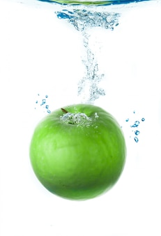 Mela fresca che cade in acqua