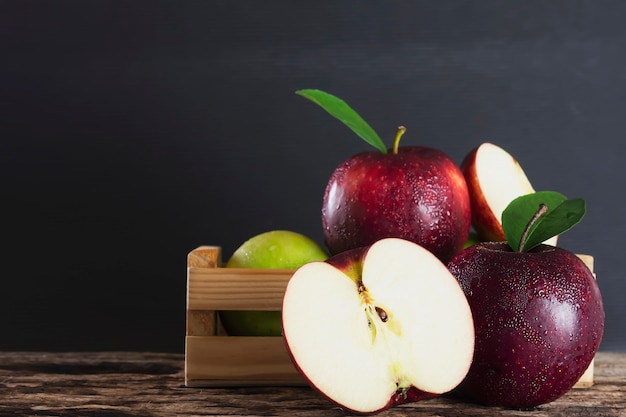 Mela fresca in scatola di legno sopra frutta nera e fresca