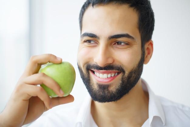 Mela mangiatrice di uomini. bella ragazza con i denti bianchi che morde la mela.