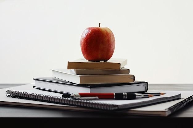 Mela, pila di libri e materiale scolastico.