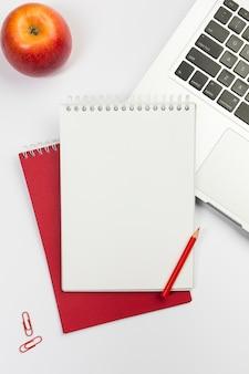 Mela rossa, blocchetto per appunti a spirale in bianco, matita di colore rosso sul computer portatile sopra priorità bassa bianca