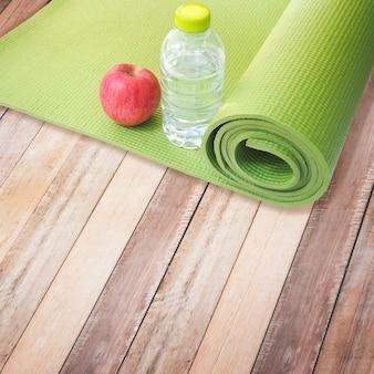 Mela rossa, bottiglia d'acqua e tappetino yoga
