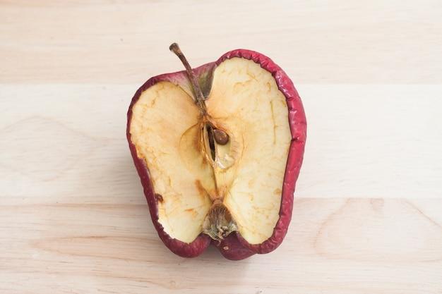 Mela rossa cattiva rovinata su fondo in legno