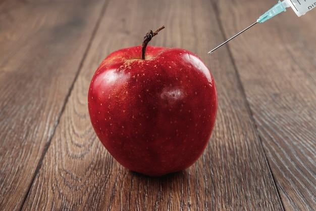 Mela rossa che inietta un ago o una siringa e pesticidi chimici su un fondo di legno