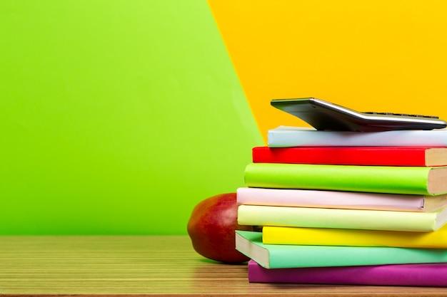 Mela rossa e vecchi libri sul ripiano del tavolo in legno