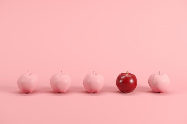 Mela rossa eccezionale tra mele dipinte rosa su sfondo rosa pastello