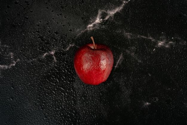Mela rossa fresca con gocce d'acqua si trova su un marmo nero, pieno di goccioline d'acqua. vista dall'alto composizione piatta.