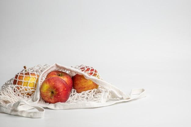 Mela rossa fresca ecologica in borsa a rete in cotone riutilizzabile naturale. concetto di rifiuti zero