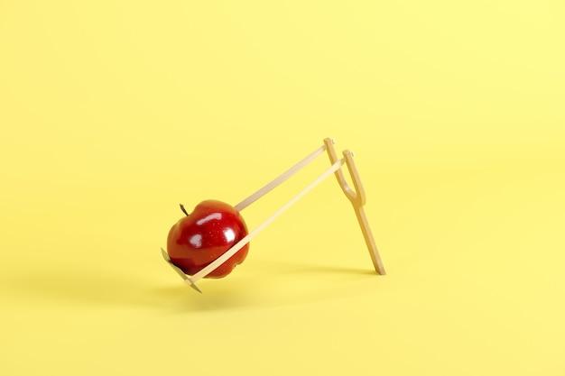 Mela rossa in una fionda su sfondo giallo