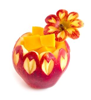 Mela rossa intagliata all'interno con frutta stile cubo di mango