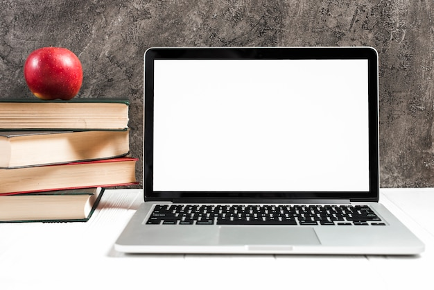 Mela rossa sul impilati di libri vicino al computer portatile sullo scrittorio bianco contro il muro di cemento