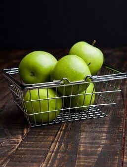 Mela sana organica verde in cestino della spesa sul bordo di legno