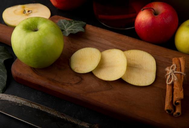 Mela verde affettata vista laterale con la foglia dell'edera della cannella su un bordo mele verdi e rosse