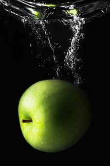 Mela verde che cade nell'acqua