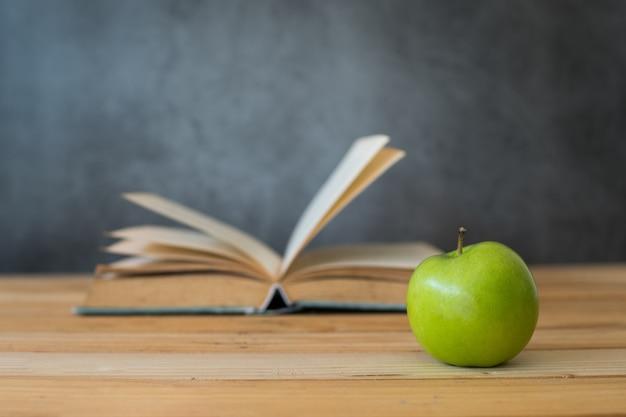 Mela verde con il libro di apertura sulla tavola di legno