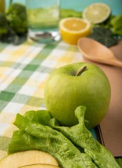 Mela verde di vista laterale con la fetta del bicchiere d'acqua della lattuga di limone e di limetta sulla tovaglia