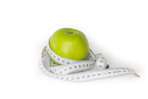 Mela verde e metro di misurazione isolati su bianco.