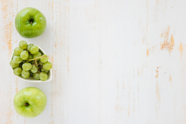 Mela verde e uva su fondo di legno bianco
