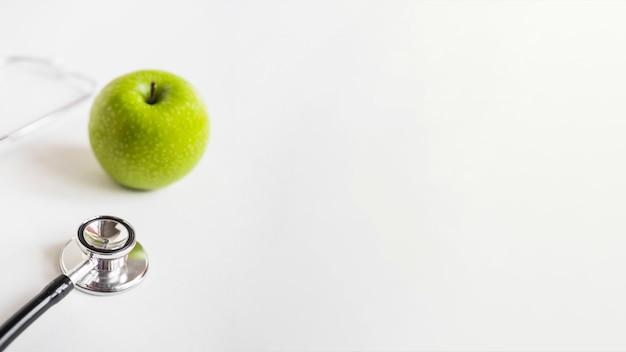 Mela verde fresca e stetoscopio isolato su sfondo bianco