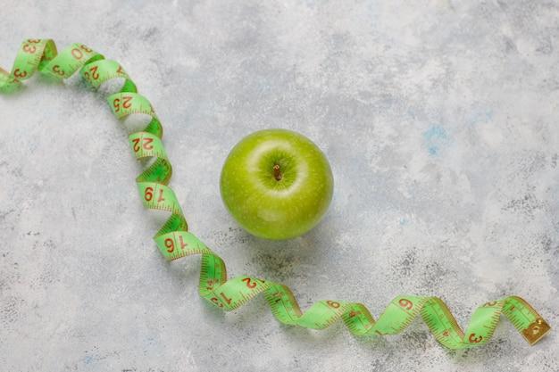 Mela verde fresca, nastro di misura e bottiglia di acqua dolce su calcestruzzo grigio