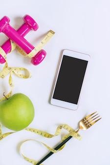 Mela verde, manubrio, metro a nastro e smart phone sul tavolo bianco. selezione di cibi sani ed esercizio fisico per una buona salute. alimenti biologici, dieta, concetto di perdere peso. vista dall'alto, copia dello spazio.