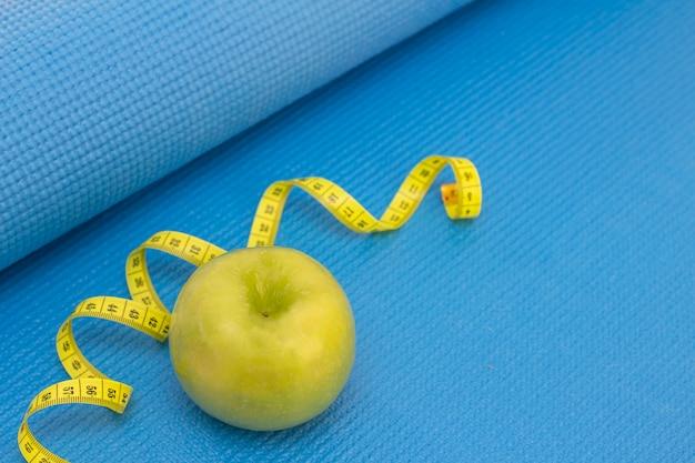 Mela verde, nastro di misurazione su un tappetino sportivo di colore blu. preparazione per la stagione estiva e il concetto di spiaggia, perdita di peso e sport