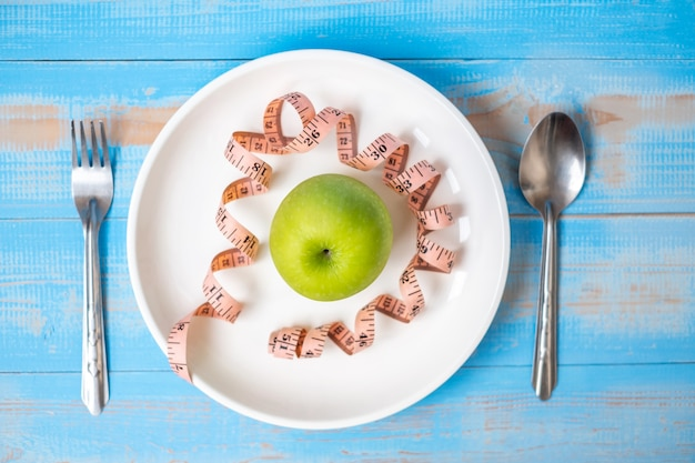Mela verde nel piatto bianco con nastro di misurazione rosa sul tavolo di legno blu