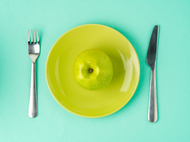 Mela verde succosa grezza matura su un piatto giallo, forcella, coltello. dieta come stile di vita.