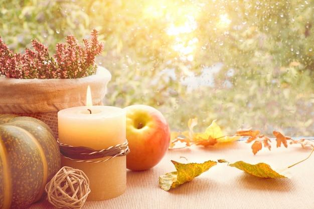 Mela, zucca, erica e foglie di autunno su un bordo della finestra